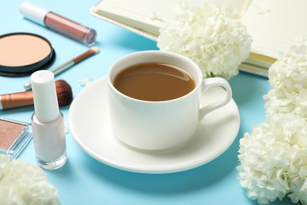Samenstelling met hortensia bloemen, koffie en cosmetica op blauwe ruimte