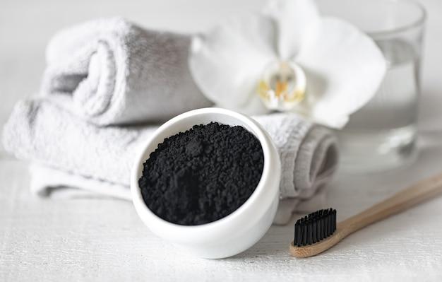 Samenstelling met houten natuurlijke tandenborstel en zwart poeder voor het bleken van tanden.
