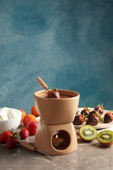 Samenstelling met ingrediënten voor chocoladefondue op grijze tafel. fondue koken
