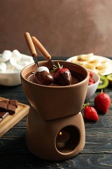 Samenstelling met ingrediënten voor chocoladefondue op houten achtergrond. fondue koken