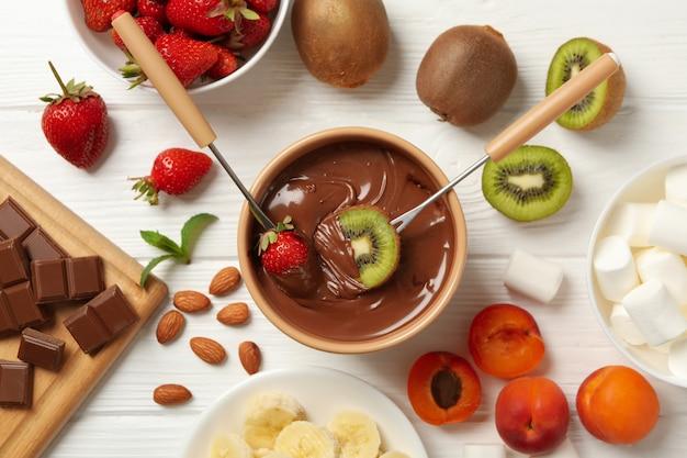Samenstelling met ingrediënten voor chocoladefondue op witte houten achtergrond. fondue koken
