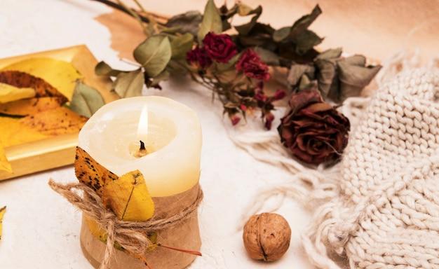 Samenstelling met kaarsen met gevallen bladeren, droge roos, trui. herfst concept