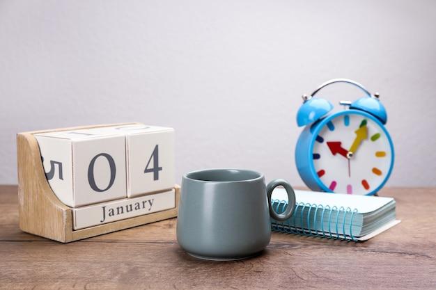 Samenstelling met kalender en kopje warme drank op houten tafel