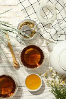 Samenstelling met kamille thee op witte houten achtergrond