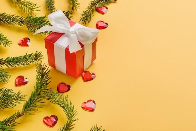 Samenstelling met kerstboomtakken, rode geschenkdoos en glazen hartjes op een gele achtergrond.