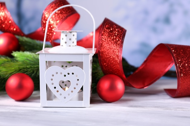 Samenstelling met kerstlantaarn, dennenboom en versieringen op lichte achtergrond