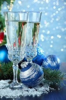 Samenstelling met kerstversiering en twee champagneglazen, op lichte achtergrond