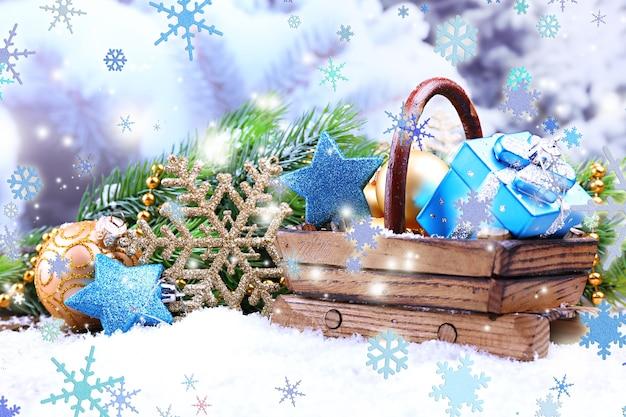 Samenstelling met kerstversiering in mand, dennenboom op lichte achtergrond