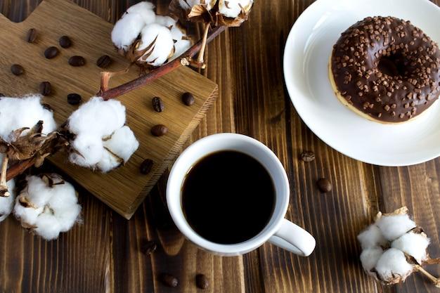 Samenstelling met koffie, tak van katoen en chocoladedoughnut op de houten achtergrond. bovenaanzicht.