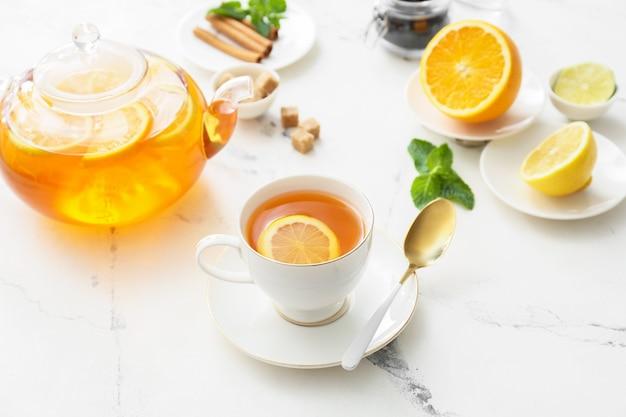 Samenstelling met kop warme gezonde drank op witte tafel