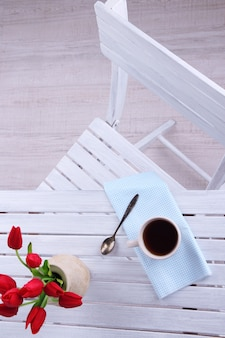 Samenstelling met kopje warme drank, kaars en bloemen op houten tafel