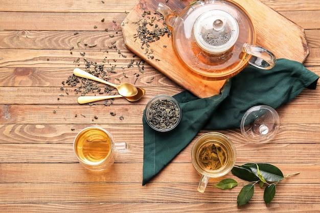 Samenstelling met kopjes groene thee en theepot op houten tafel