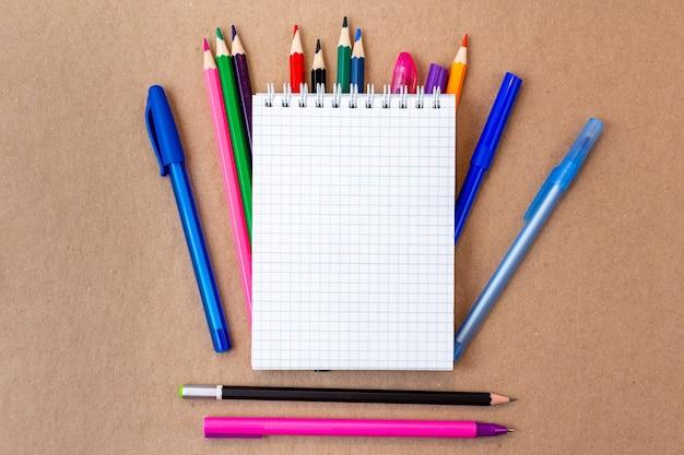 Samenstelling met leeg notitieboekje en kleurrijke potloden