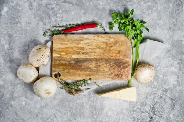 Samenstelling met lege houten plank en groenten op keukentafel