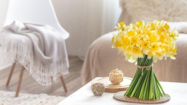 Samenstelling met lentebloemen in een gezellig woonkamerinterieur. het concept van decor en comfort.