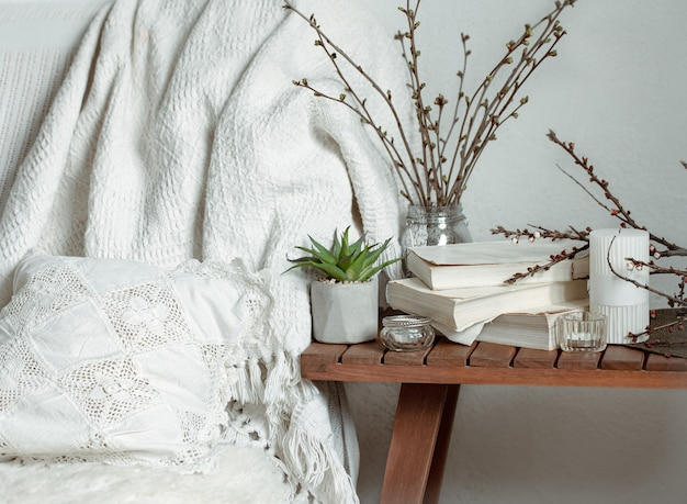 Samenstelling met lentetakken, boeken en kaarsen in het interieur van de kamer.