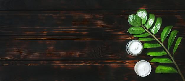 Samenstelling met lichaamsverzorgingsproducten, bosje en groen blad op oude houten lijst, hoogste mening