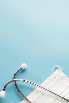 Samenstelling met medische stethoscoop, wegwerp gezichtsmaskers op een blauwe tafel. bovenaanzicht. vrije exemplaarruimte.