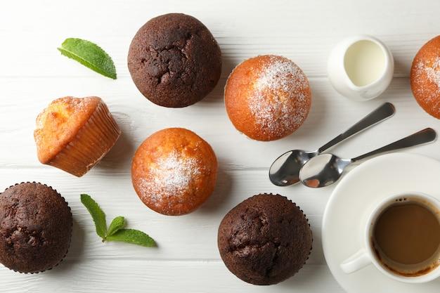 Samenstelling met muffins en cacaodrank op witte houten achtergrond