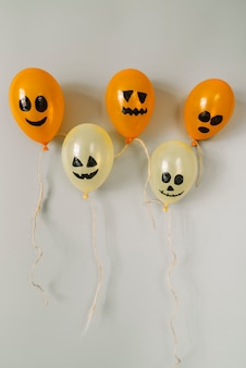 Samenstelling met oranje en witte luchtballons met enge gezichten