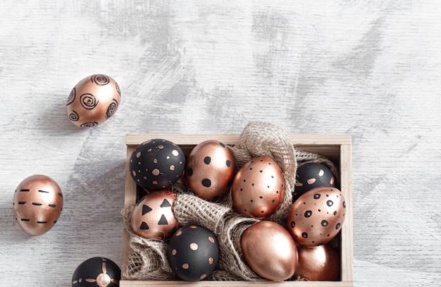 Samenstelling met paaseieren geschilderd in gouden en zwarte kleuren met ornamenten