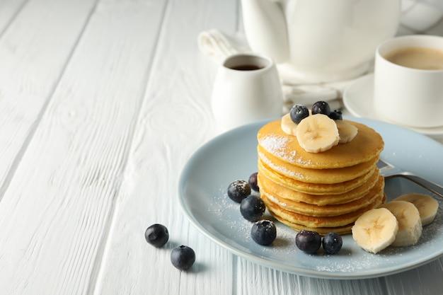 Samenstelling met pannenkoeken, bananen en bosbessen op houten tafel. zoet ontbijt