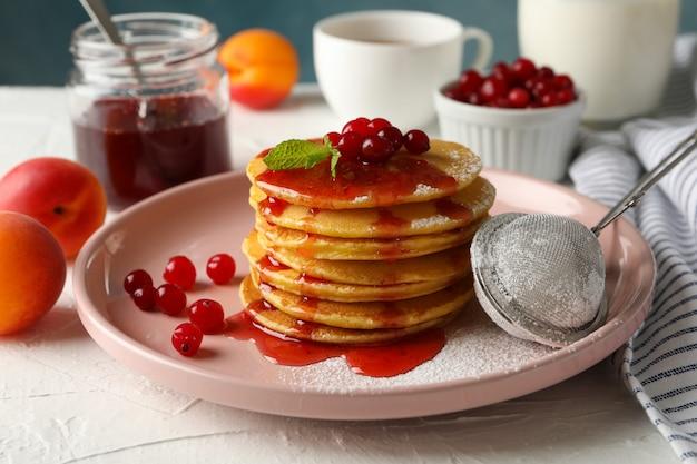 Samenstelling met pannenkoeken met jam en cranberry op witte tafel