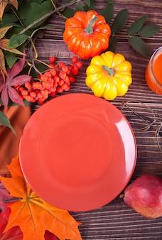 Samenstelling met plaat, pompoen, herfstbladeren, kaars en rode peren op houten tafel, plat leggen