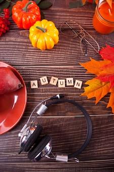 Samenstelling met pompoen, herfstbladeren, koptelefoon, kaars en rode peren op houten tafel, plat leggen