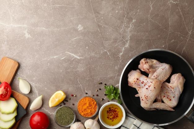 Samenstelling met rauwe kip en kruiden op grijs. kip koken