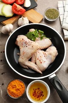 Samenstelling met rauwe kip en specerijen op grijze ruimte. kip koken