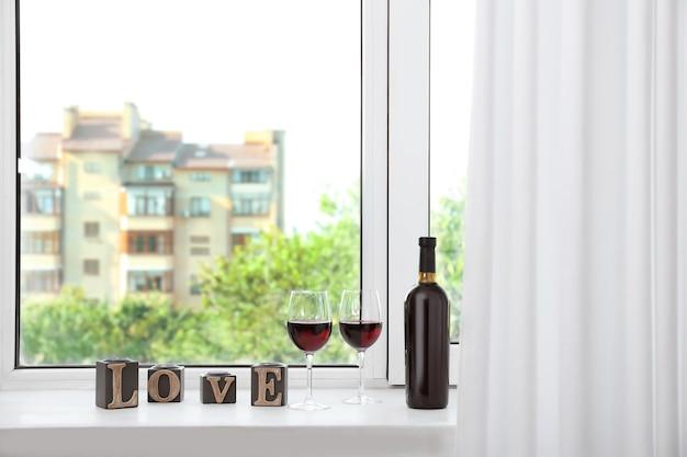 Samenstelling met rode wijn en woord love op vensterbank