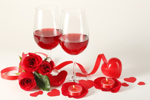 Samenstelling met rode wijn in glazen, rode rozen, lint en decoratieve harten