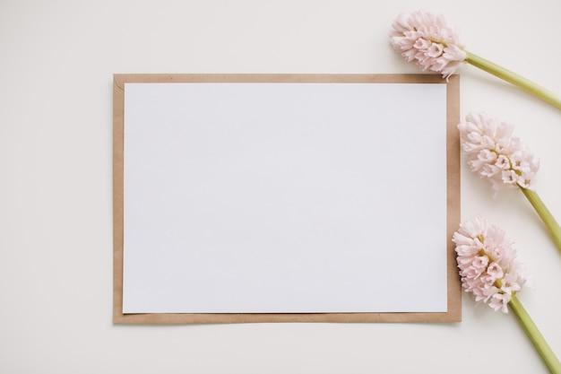 Samenstelling met roze bloemen en blanco papieren kaart, mockup, uitnodigingen.