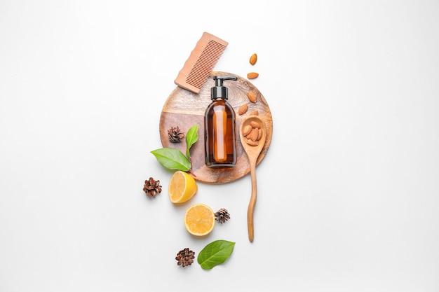 Samenstelling met shampoo, natuurlijke ingrediënten en kam op witte achtergrond