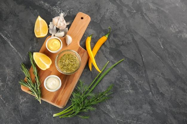 Samenstelling met smakelijke sauzen op grijze tafel