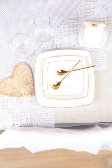 Samenstelling met theepot, schotel en lepels op houten tafel