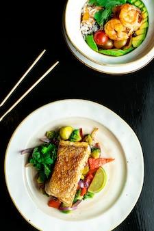 Samenstelling met twee gerechten op donkere achtergrond. snoekbaarsfilet met groenten en boeddha schaal met garnalen en avocado. heerlijk gezond voedsel voor dieet. zeevruchten. foodfoto voor recept of menu