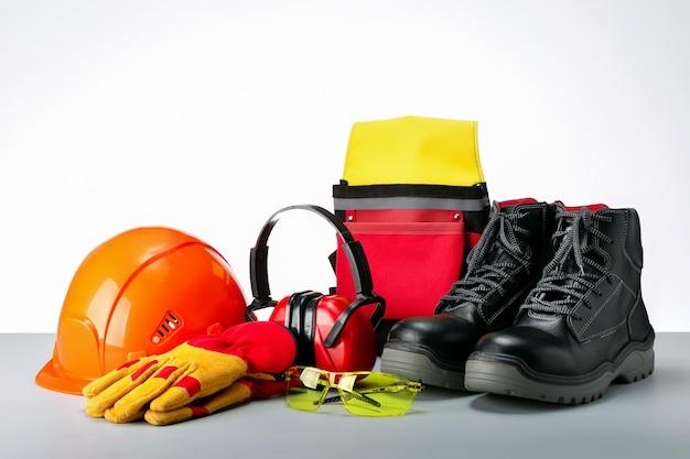 Samenstelling met veiligheidsuitrusting, beschermende schoenen, veiligheidsbril, handschoenen en gehoorbescherming.