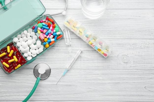 Samenstelling met verschillende pillen, spuit en stethoscoop op houten tafel