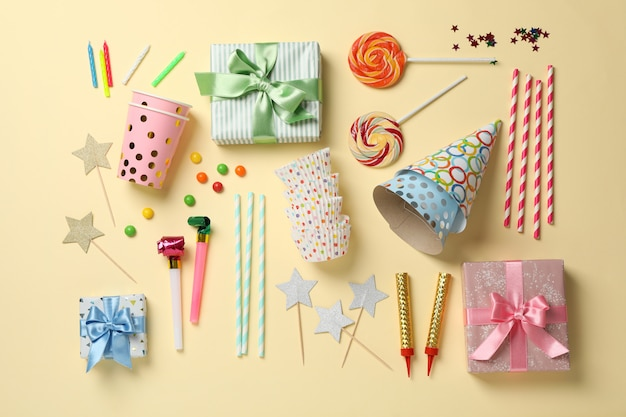 Samenstelling met verschillende verjaardag accessoires op beige achtergrond, bovenaanzicht