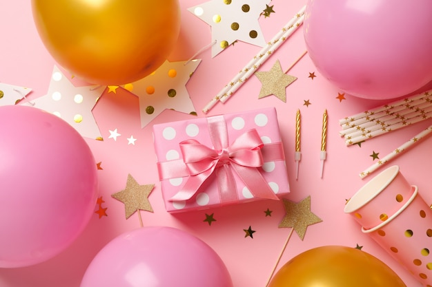 Samenstelling met verschillende verjaardag accessoires op roze achtergrond, bovenaanzicht