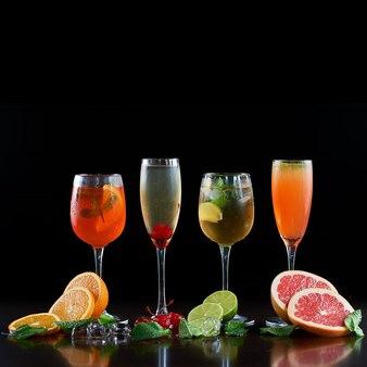 Samenstelling met vier verschillende vormen kristallen cocktailglazen met koude dranken, sinaasappel