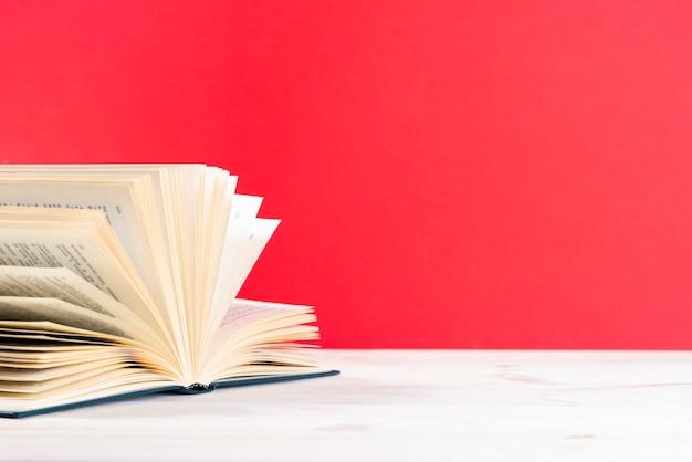 Samenstelling met vintage oude boek met harde kaft, dagboek, gewaaide pagina's op houten dek tafel