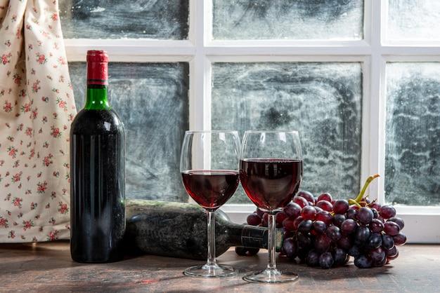 Samenstelling met wijnglazen, druiven en flessen rode wijn