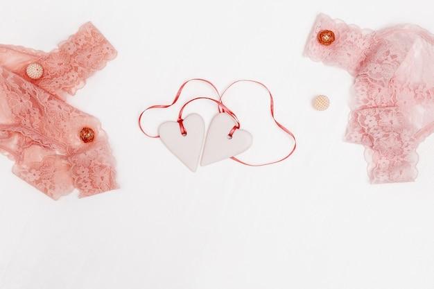 Samenstelling met witte harten, de lingerie van het vrouwenkant op witte achtergrond.