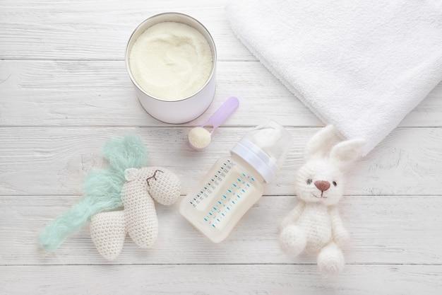 Samenstelling met zuigfles van babymelk formule op houten tafel