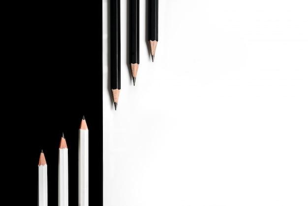 Samenstelling met zwarte potloden op een witte achtergrond en witte potloden op een zwarte achtergrond