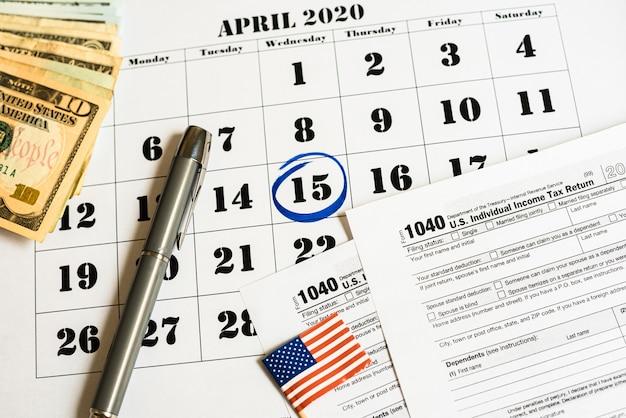 Samenstelling op de dag van belastingbetaling in april met bankbiljetten en belastingformulier.