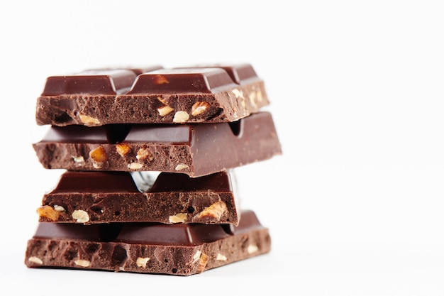 Samenstelling stapel tegels van donkere chocolade met noten close-up op een witte achtergrond geïsoleerd